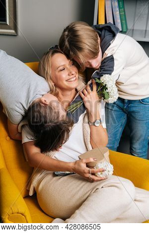 Portrait Of Two Loving Cute Small Kid Sons Hugging Kissing Happy Young Mom Congratulating With Chris