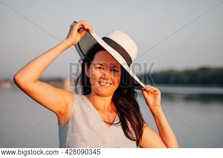 Portrait Of A Woman In A Straw Hat, A Close-up Portrait Of A Happy Asian Woman Holding The Brim Of A