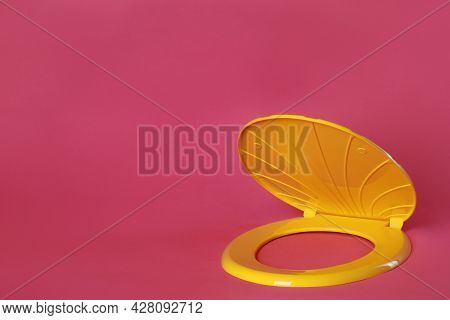 New Yellow Plastic Toilet Seat On Pink Background, Space For Text