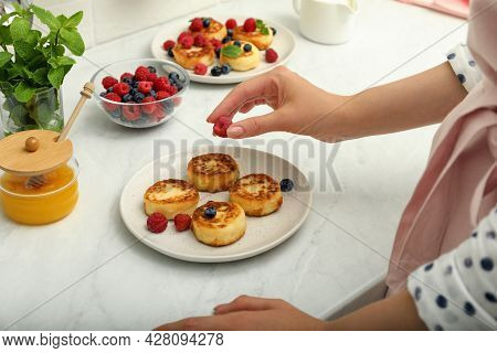 Woman Decorating Delicious Cottage Cheese Pancakes With Fresh Berries At White Countertop, Closeup