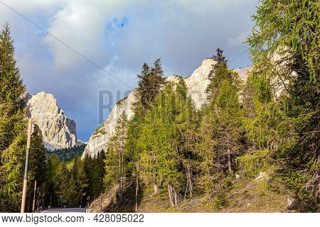 Magnificent mountain range in the Eastern Alps - Dolomites. Picturesque sunset in the colorful rocks of the Dolomites. Slender pines and spruces grow at the foot of the mountains.