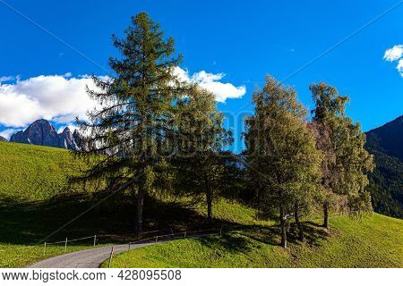 Magnificent Dolomites on a sunny autumn day. Europe, Val de Funes. Tyrol, Italy. Green pastures and mountain road are fenced with neat fences