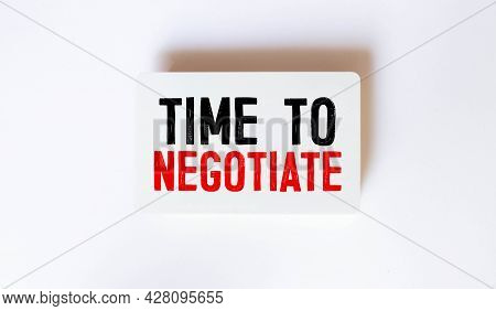 A Business Card With The Text Time To Negotiate Lies On A Wooden Office Table Among Office Supplies.