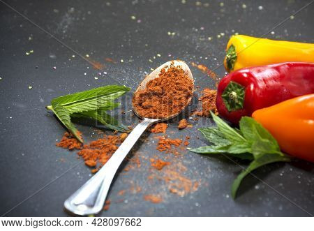 Red Paprika Powder In Tablespoon With Bell Papers On A Black Background
