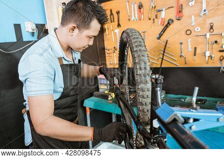 Male Bicycle Mechanic In Apron Lubricating Chain While Repairing Problem On Bicycle