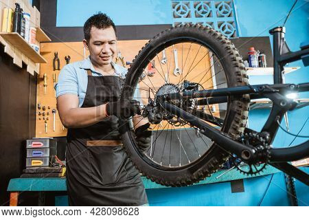 Bicycle Mechanic In Aprons Tightens Spokes While Fixing Problems