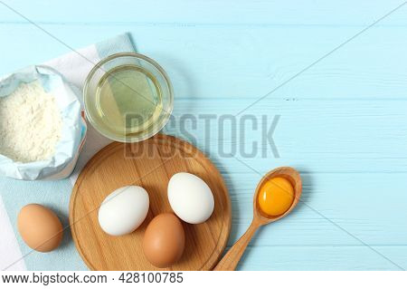 Chicken Eggs And A Whisk On The Table Top View.