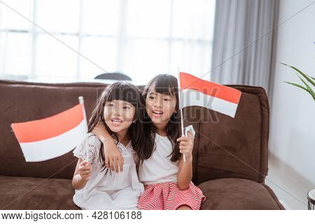 Indonesian Girl Holding Indonesian Flag At Home