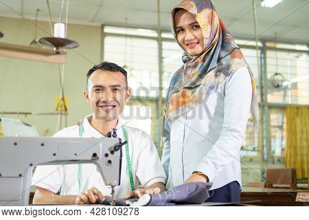 Female Supervisor Stands Next To The Employee Working With The Sewing Machine
