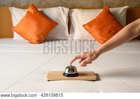Close-up Of Guest Hand Trying To Ringing Hotel Bell In Hotel Bedroom. Hotel Bell Is Normally Use To