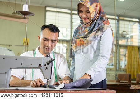 Veiled Supervisor Stands To Watch Over Employees Working On Sewing Machines