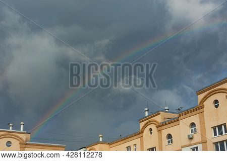 A Rainbow Over The House Against The Background Of Dark Storm Clouds. The Concept Of A Storm, Worsen