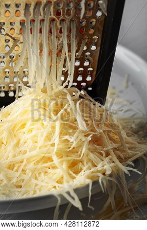 Grated Cheese And Grater. Concept: Italian Cuisine, Cheese, Restaurant, And Food. Selective Focus.