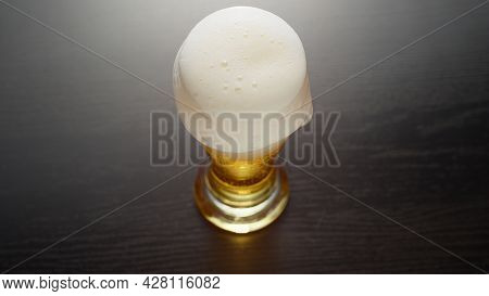 Beer in glass overflowed. Half pint of frothy fresh lager beer on table. Foam goes over the edge. Top view.