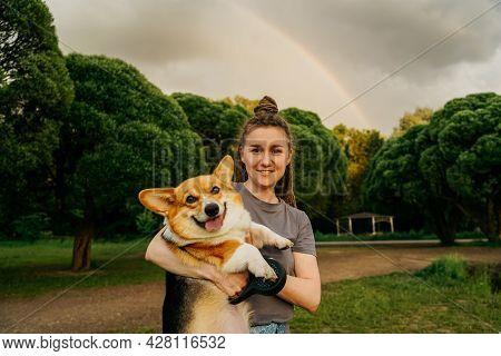 Woman With Dreadlocks Holding Small Dog Corgi.