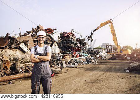 Portrait Of Junkyard Worker Standing In Scrap Metal Recycling Center.