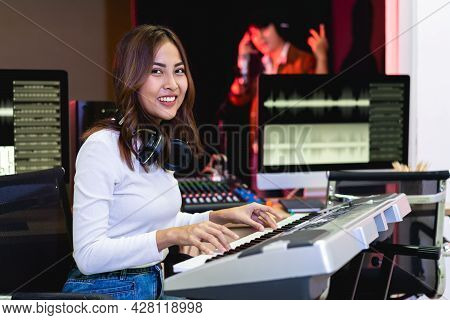 Asian Producer Woman In White Shirt Standing By Sound Mixing Console. Happy Female Music Composer Ar