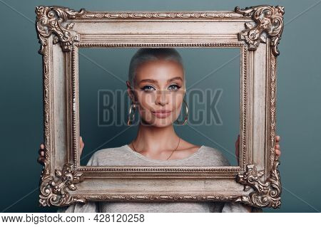 Millenial Young Woman With Short Blonde Hair Holds Gilded Picture Frame In Hands. Female Face Portra