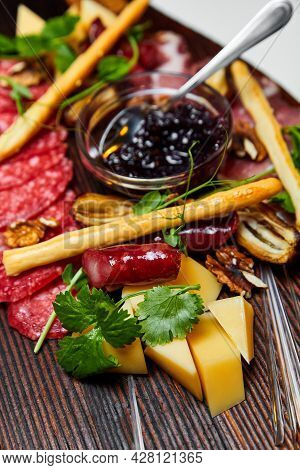 Assorted Cheeses And Meat Delicacies On Wooden Board. Close-up, Selective Focus.