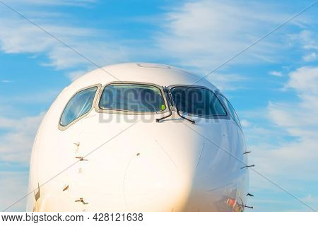 Passenger Airplane Nose Cockpit In Blue Clouds Evening Sky