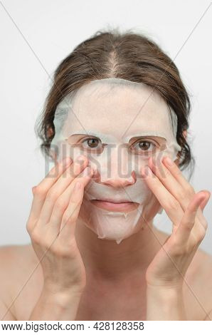 The Woman Puts On A Moisturizing Paper Mask. Facial Skin Care. Portrait Of A Beautiful Young Woman I
