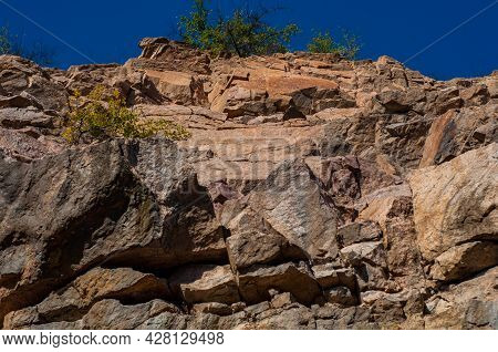Granite Rocks Close-up On Background Blue Sky With White Clouds, Green Leaves On Treetops.