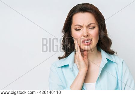 Young Woman Suffering From Strong Teeth Pain, Touching Cheek With Hand. Dentistry Concept
