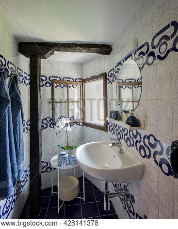 Small bathroom with sink and a round mirror. There is a coffee table with an orchid and two vases. Bright window. Nobody inside