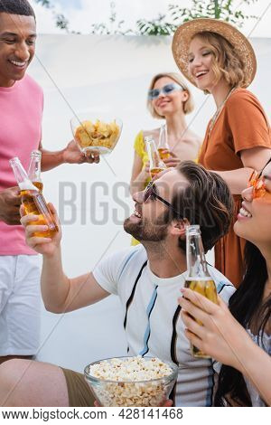 Happy Interracial Men Clinking With Bottles Of Beer Near Smiling Women