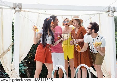 Excited Multicultural Friends With Snacks And Beer Having Party In Patio At Poolside