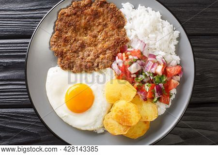 Authentic Silpancho Bolivian Food From Rice Potatoes, Beef, And Fried Eggs Are Topped With Fresh Sal