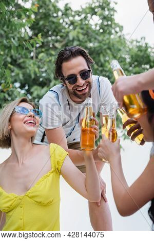 Happy Friends In Sunglasses Clinking Bottles Of Beer During Summer Party