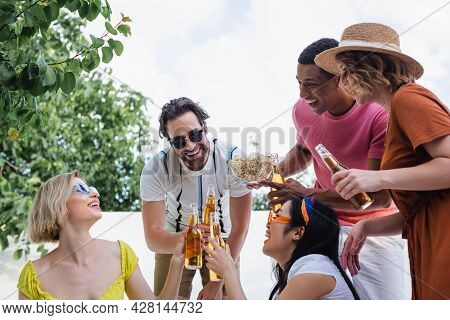 Happy Multicultural Friends Clinking Bottles Of Beer Near African American Man With Bowl Of Chips