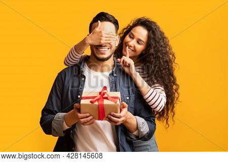 Surprise Present. Romantic Young Arab Woman Covering Boyfriends Eyes And Giving Gift
