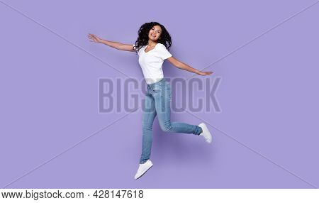 Woman Jumping Posing In Mid-air Expressing Positive Emotions, Purple Background