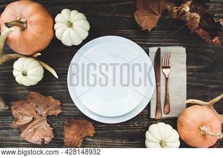 Holiday Place Setting With Plate, Napkin, Antlers And Silverware On A Thanksgiving Day Decorated Tab