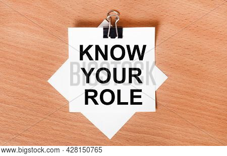 On A Wooden Table Under A Black Paper Clip Lies A Sheet Of White Paper With The Text Know Your Role
