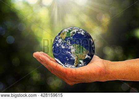Hand Holding Planet Earth On Blurred Green Nature With Sunlight Background, Elements Of This Image F