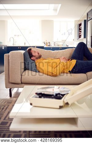 Relaxed Man Lying On Sofa At Home Listening To Vinyl Record On Record Player