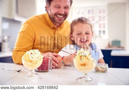 Father And Daughter In Kitchen Decorating Ice Cream Dessert With Cream And Sprinkles