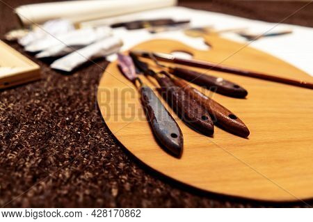 Different Types Of Palette Knife, Thin Brush And Tubes Lie On A Wooden Palette. Art Materials On Bro