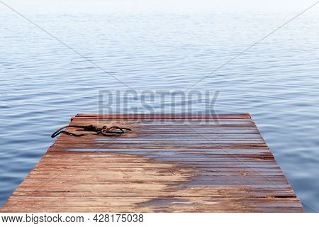 Wet Rope Lays At The End Of Small Wooden Pier, Abstract Background Photo