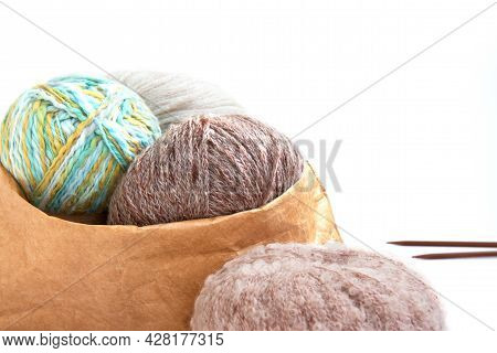Balls Of Yarn In Nude Colors In A Craft Bag And Knitting Needles On A Bright Background. Craft On Wh