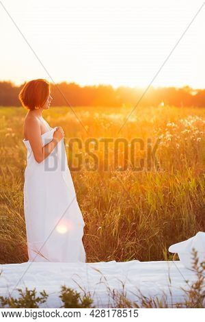 Charming Caucasian Woman 30-35 Years Old In A Field At Sunset In Summer Side View