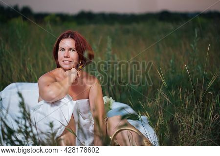 Charming Caucasian Woman 30-35 Years Old Sitting In The White Bed In A Field At Sunset In Summer