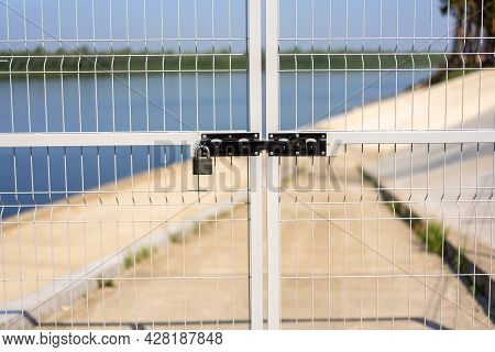 The Fence Is Vertical Metal (gate) On The Background Of The River, The Sky, Closed With A Padlock. A