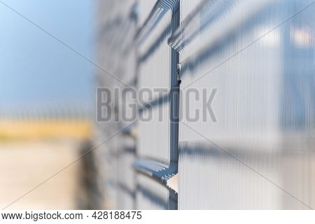 Elements Of The Metal Vertical Fence Of The Park, A Summer Sunny Day, The Background Is Very Blurred