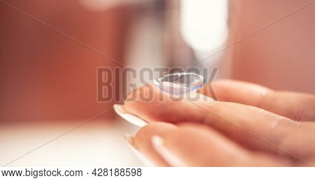 Contact Lens On The Fingers Of A Young Woman Before Application To The Eye.