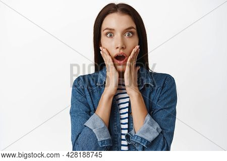 Close Up Of Shocked Adult Woman Gasp, Stare Startled And Speechless At Camera, Drop Jaw And Hold Han