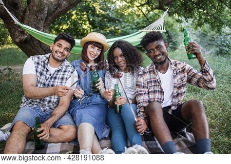 Group Of Four Happy Friends Sitting On Soft Plaid At Summer Garden, Drinking Cold Beer And Eating Gr